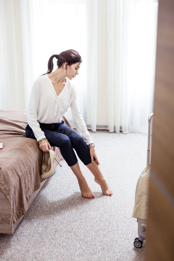 Piękna atrakcyjna kobieta patrzeje jej nogi zdjęcie royalty free