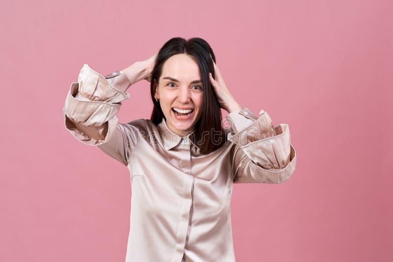 Piękna atrakcyjna młoda brunetki kobieta ono uśmiecha się szczęśliwie i śmia się Pracowniany portret odizolowywający na różowym t zdjęcie royalty free
