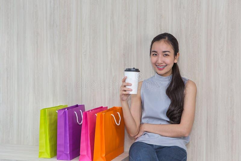 Piękna Azjatycka dziewczyna, młody kupujący, kolorowa papierowa torba i filiżanka, fotografia royalty free