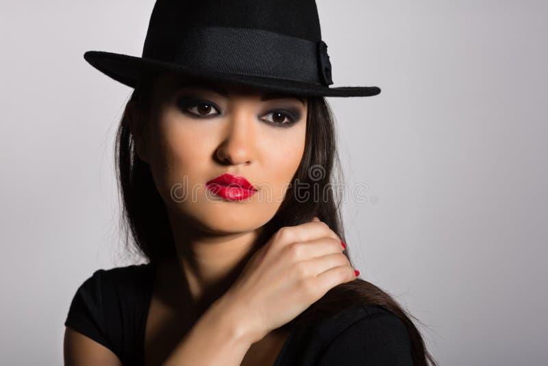 Piękna Azjatycka dziewczyna w czarnym kapeluszu fotografia stock