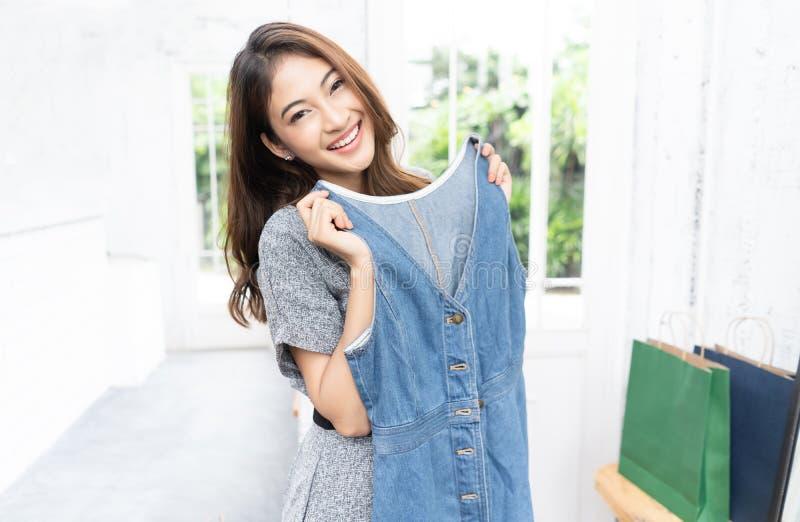 Piękna Azjatycka dziewczyny próba być ubranym jej suknię odziewa przy ona domowa i patrzeje kamerę po tym jak iść robić zakupy z  obrazy royalty free