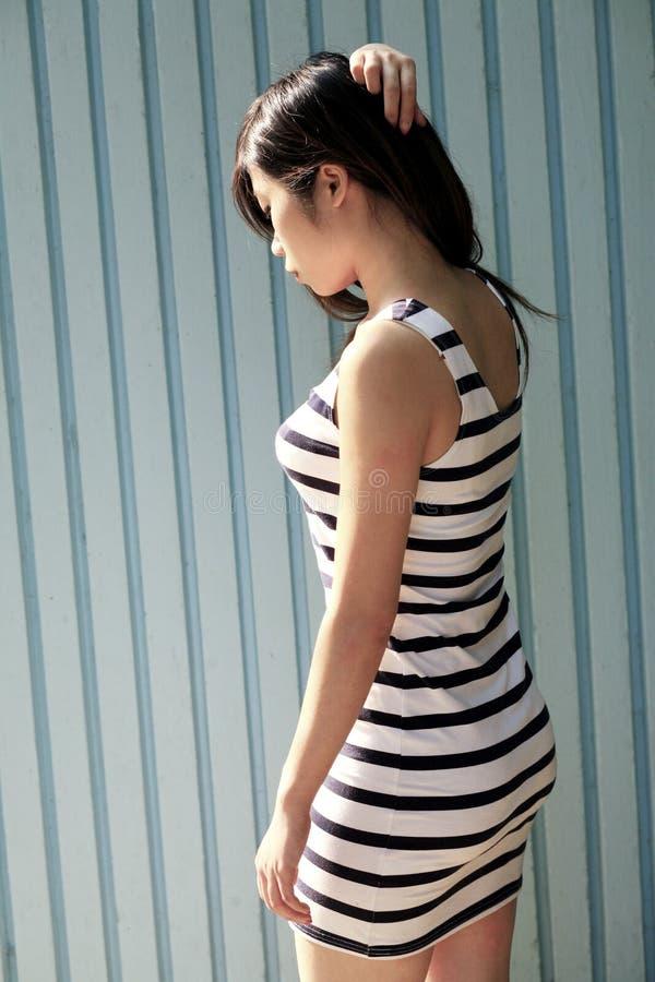 Piękna Azjatycka kobieta patrzeje strona jest ubranym pasiastą suknię obraz stock