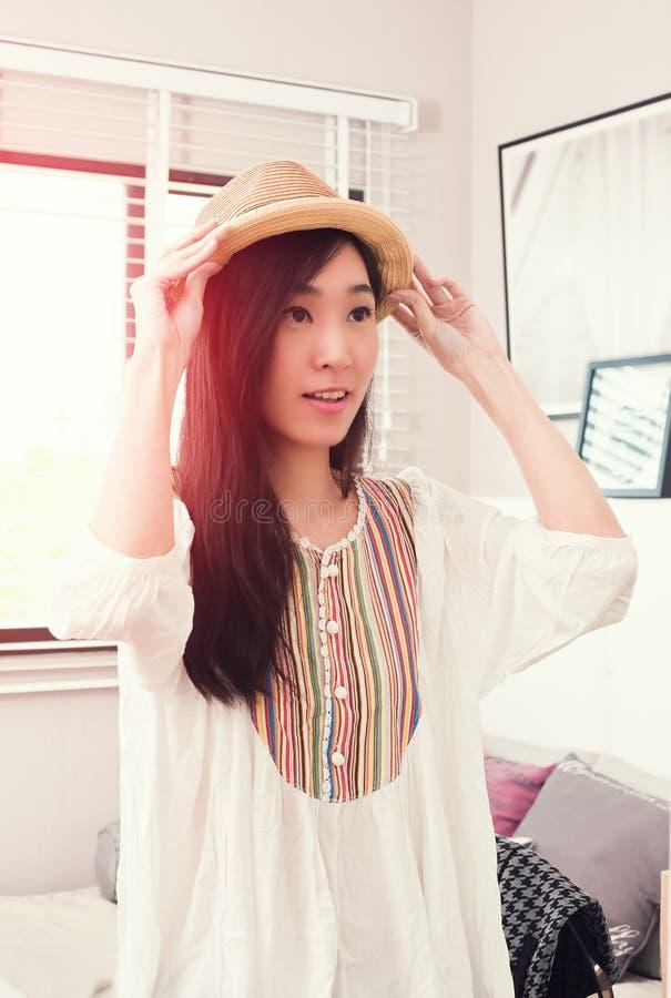 Piękna Azjatycka kobieta próbuje Panama kapelusz przed lustrem zdjęcie stock