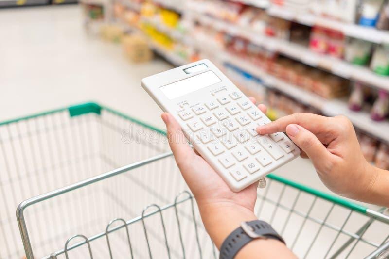 Piękna Azjatycka kobieta trzyma kalkulatora kalkulować ceny redukcję w supermarkecie i koszt Pojęcie cena fotografia stock