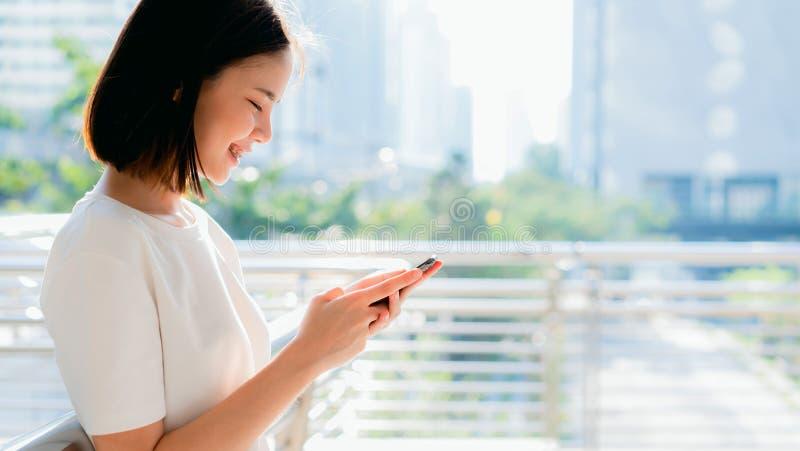 Piękna Azjatycka kobieta używa smartphone i pozycję w budynku biurowym obrazy royalty free