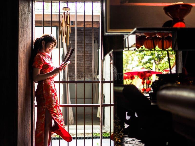 Piękna Azjatycka kobieta W Cheongsam sukni, Czerwona chińczyk suknia Stoi przed wejściem który Chińskiego wnętrze obrazy stock