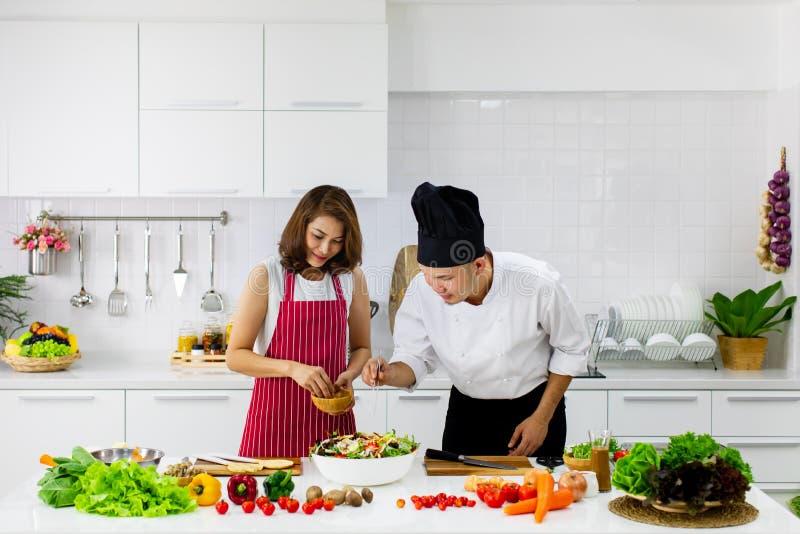 Piękna Azjatycka kobieta w czerwonym fartucha uczenie dlaczego gotować i mieszać obrazy royalty free