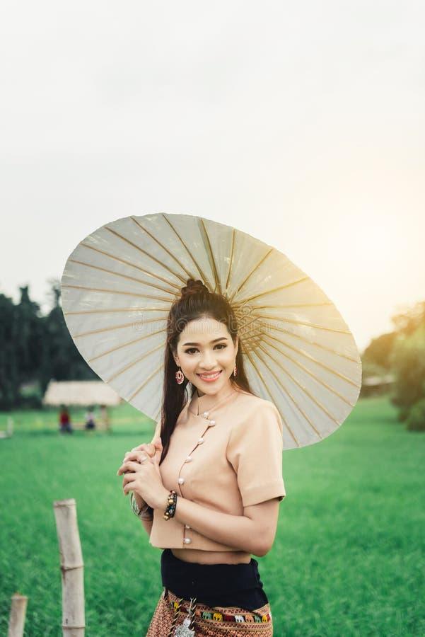 Piękna Azjatycka kobieta w miejscowy sukni mienia papieru parasolowej pozycji i cieszy się naturalnego na bambusa moście fotografia stock