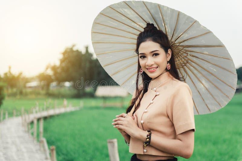 Piękna Azjatycka kobieta w miejscowy sukni mienia papieru parasolowej pozycji i cieszy się naturalnego na bambusa moście zdjęcie stock