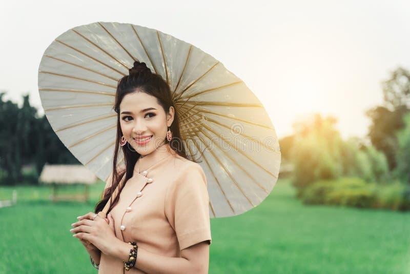 Piękna Azjatycka kobieta w miejscowy sukni mienia papieru parasolowej pozycji i cieszy się naturalnego na bambusa moście zdjęcia stock