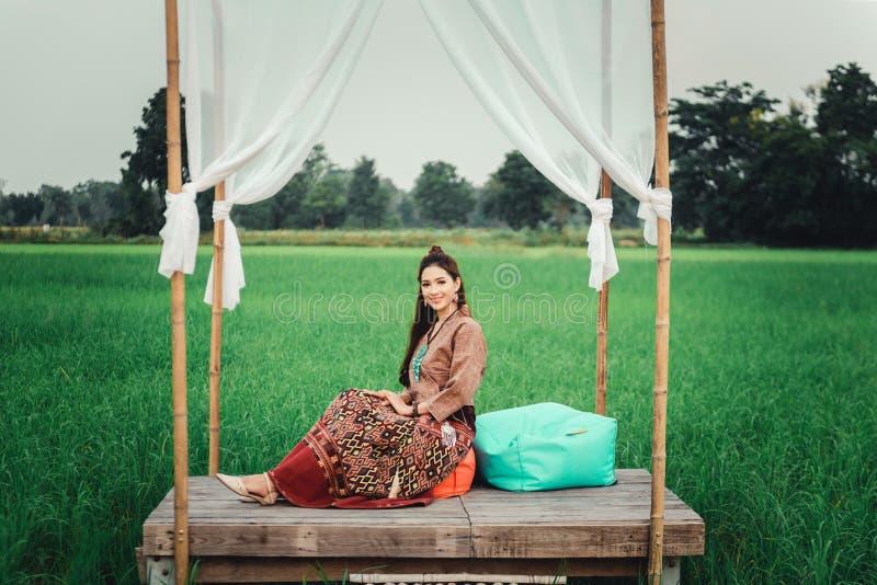 Piękna Azjatycka kobieta w miejscowy sukni obsiadaniu w małym bambusowym pawilonie z sukienną dekoracją i cieszy się natural zdjęcia royalty free
