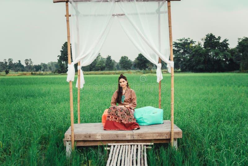 Piękna Azjatycka kobieta w miejscowy sukni obsiadaniu w małym bambusowym pawilonie z sukienną dekoracją i cieszy się natural zdjęcia stock
