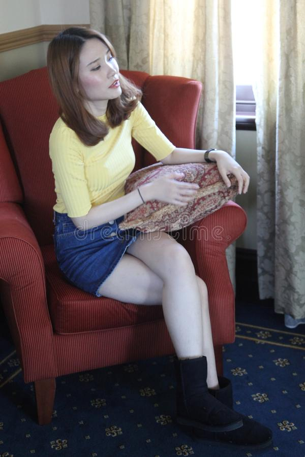 Piękna Azjatycka kobieta z żółty odgórny patrzeć strona obraz royalty free