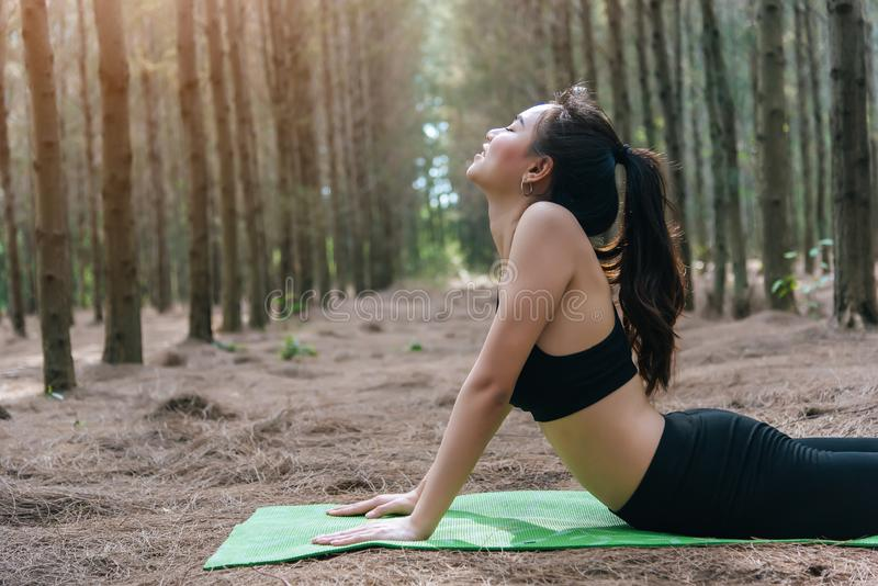 Piękna Azjatycka młoda kobieta robi joga i zaszaluje na zieleni macie w lasowym pojęciu ćwiczenia i medytacji Pokojowy i fotografia royalty free
