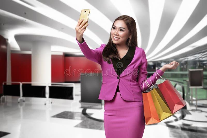 Piękna azjatykcia biznesowa kobieta z torba na zakupy bierze selfie zdjęcie stock