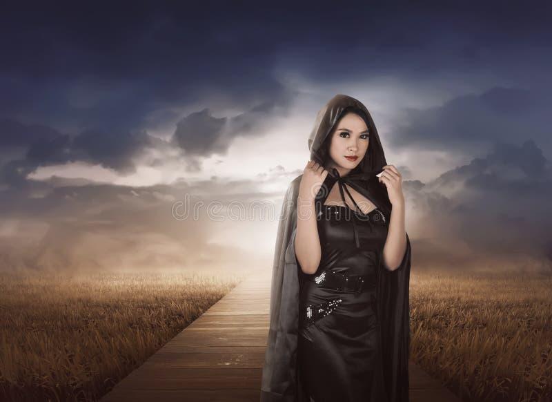 Piękna azjatykcia czarownicy kobieta z czarnym kapiszonem fotografia royalty free