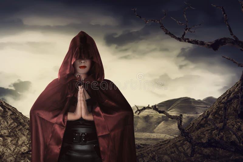 Piękna azjatykcia czarownicy kobieta z czerwonym peleryny modleniem obrazy royalty free