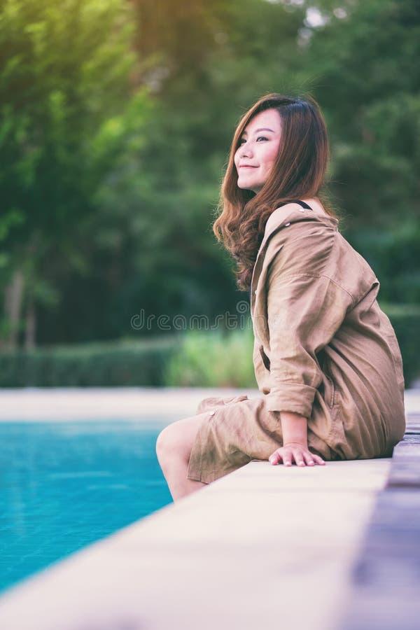 Piękna azjatykcia kobieta cieszył się obsiadanie basenem zdjęcia royalty free