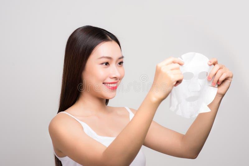 Piękna azjatykcia kobieta stosuje papieru prześcieradła maskę na jej twarzy whit zdjęcie royalty free