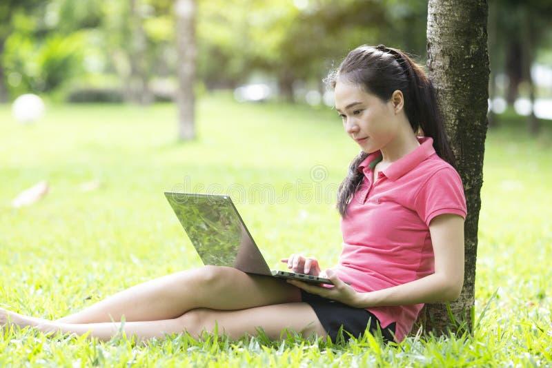 Piękna azjatykcia kobieta używa laptop w parku obrazy royalty free