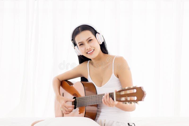 Piękna azjatykcia kobieta wręcza bawić się gitarę akustyczną w sypialni, Relaksujący czas zdjęcia stock