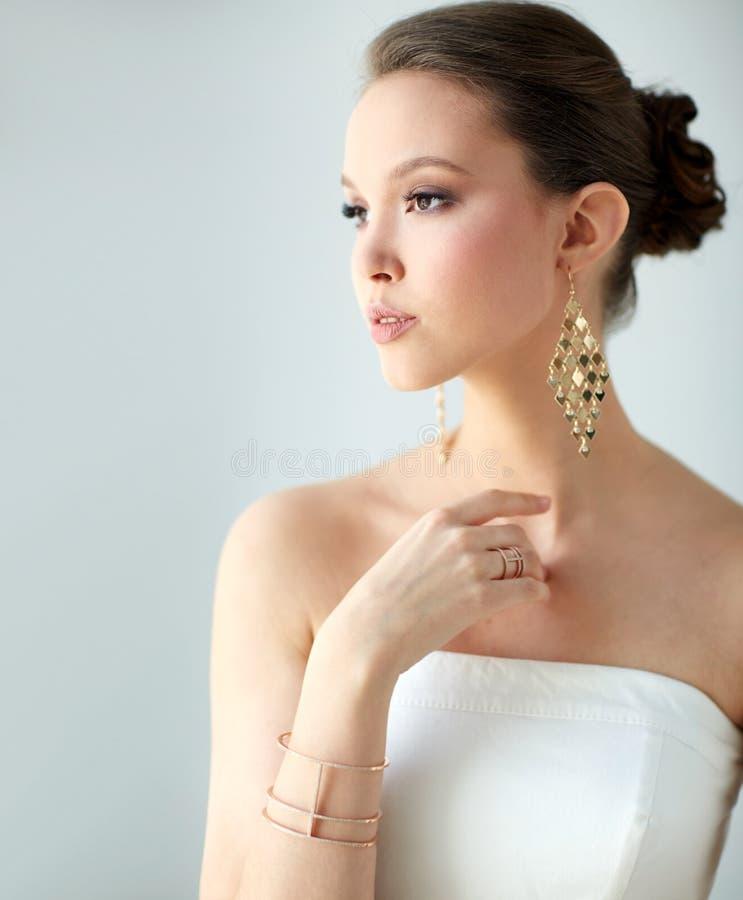 Piękna azjatykcia kobieta z kolczykami i bransoletką fotografia royalty free