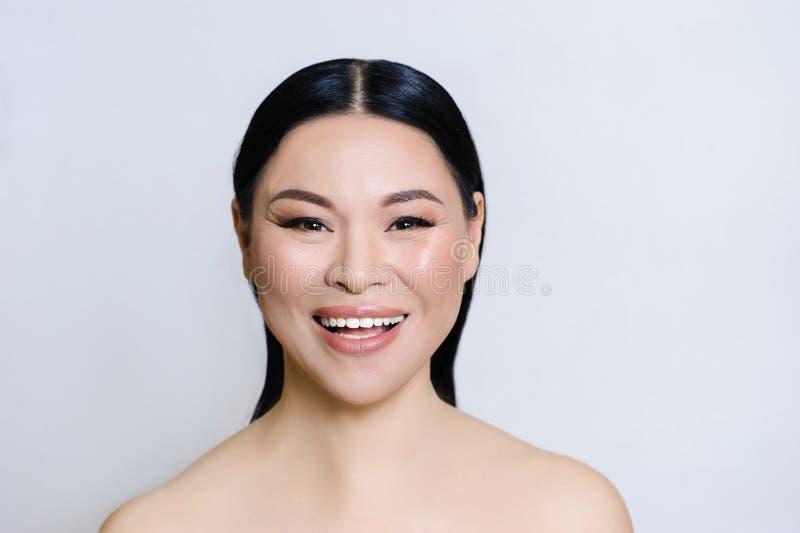 Pi?kna azjatykcia kobiety twarz z czyst? ?wie?? sk?r?, nagim makeup, kosmetologi?, opiek? zdrowotn?, pi?knem i zdrojem, obraz stock