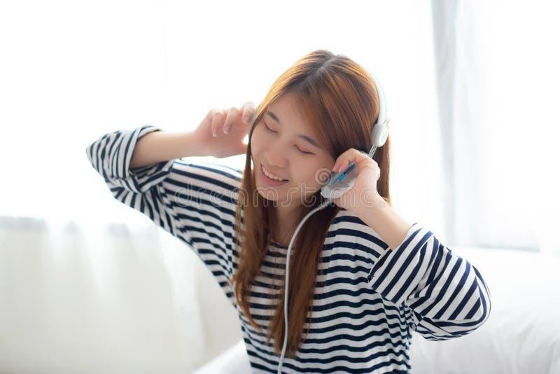 Piękna azjatykcia młoda kobieta cieszy się i zabawa słucha muzykę z głową fotografia stock