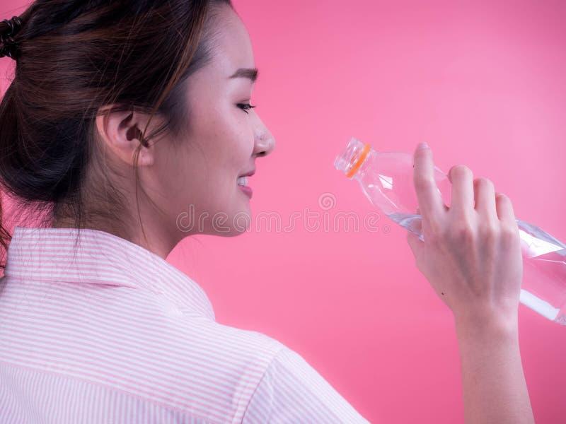 Piękna azjatykcia młoda kobieta pije butelkę odizolowywającą na różowym tle woda zdjęcie stock