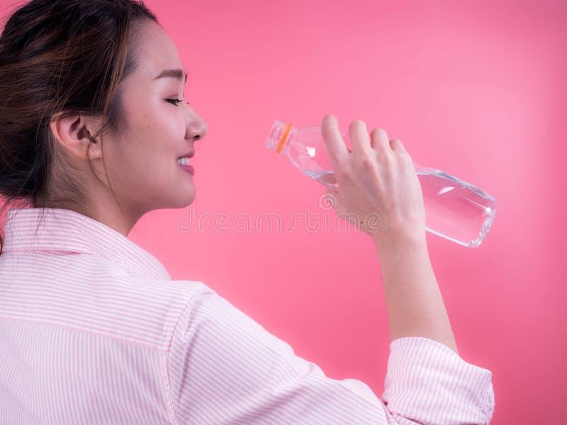 Piękna azjatykcia młoda kobieta pije butelkę odizolowywającą na różowym tle woda obraz royalty free