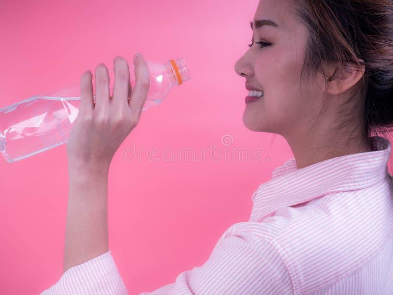 Piękna azjatykcia młoda kobieta pije butelkę woda na różowym tle obraz stock