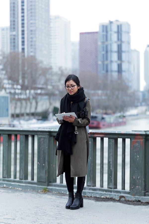 Piękna azjatykcia młoda kobieta używa jej cyfrową pastylkę przed wonton rzeką w Paryż obraz stock