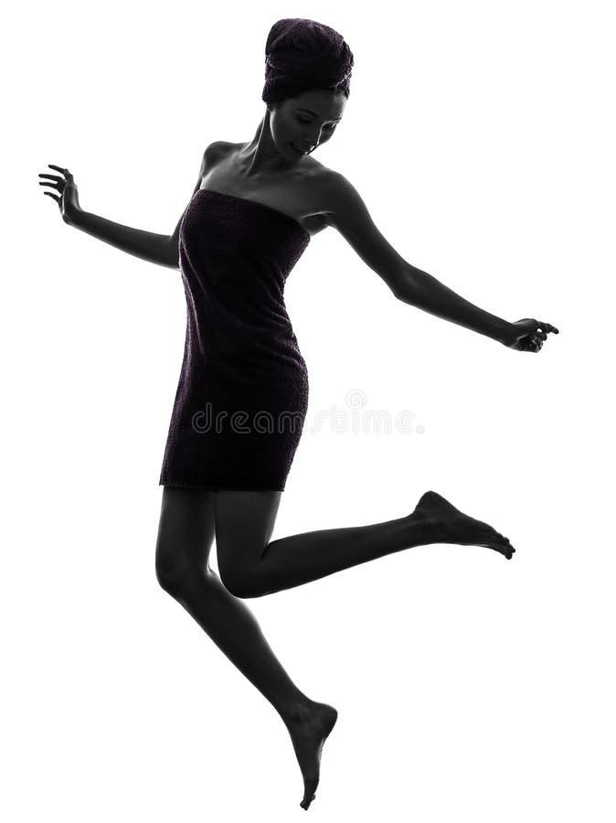 Piękna azjatykcia młoda kobieta zawijał ręcznikowego skokowego szczęśliwego silhouet zdjęcie stock