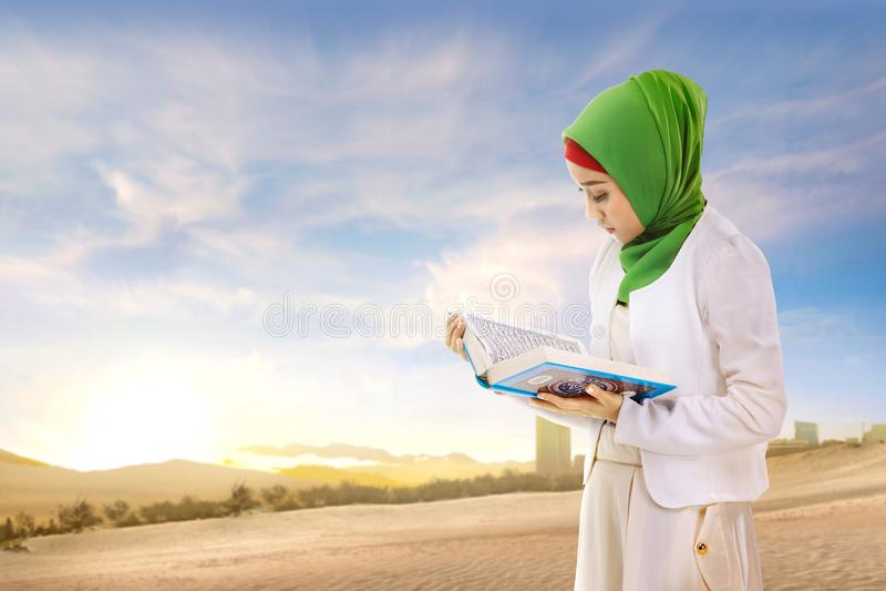 Piękna azjatykcia muzułmańska kobieta w przesłony czytaniu i pozycji koran na piasku zdjęcia royalty free