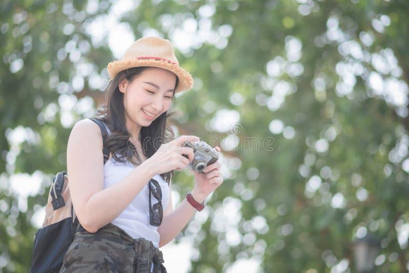 Piękna azjatykcia solo turystyczna kobieta cieszy się brać fotografię retro kamerą przy turystycznym zwiedzającym punktem obraz stock