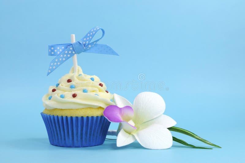 Piękna błękitna babeczka z storczykowym kwiatem na błękitnym tle obrazy stock
