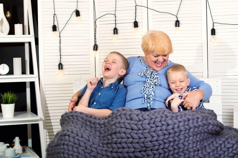 Piękna babcia i dwa wnuka siedzimy na kanapie pod trykotową merynosową wełny koc i zabawę szczęśliwa rodzina obrazy royalty free