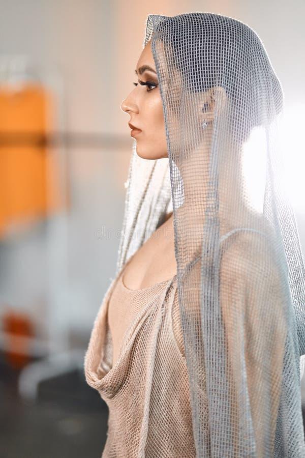 Piękna balerina pozuje w popielatym kostiumu z przylądkiem na głowie w baletniczym studiu zdjęcie royalty free