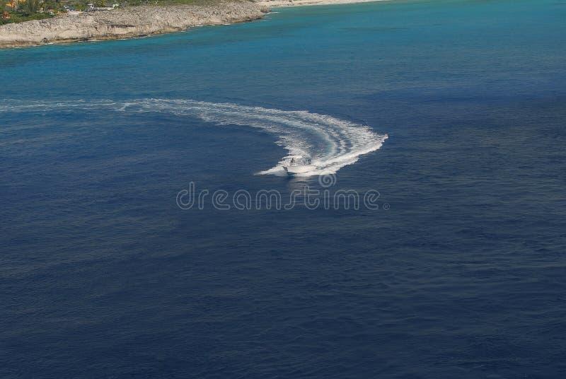 Piękna biała przyjemności łódź z kierowcą opuszcza szerokiego kilwater w morzu zdjęcia royalty free