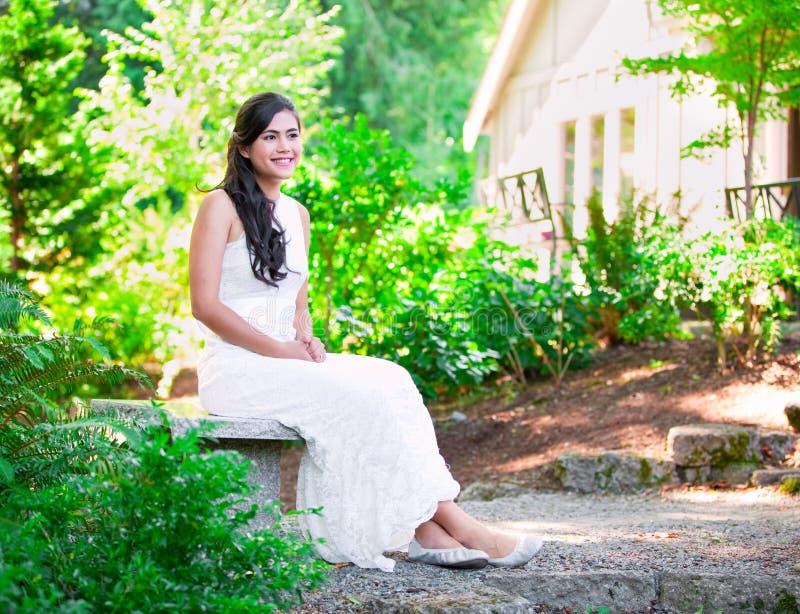 Piękna biracial panna młoda w biel koronki ślubnej sukni obsiadaniu dalej zdjęcia royalty free