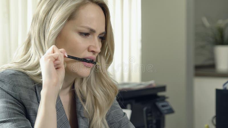 Piękna biznesowa kobieta gryźć jej ołówek w biurze zdjęcia royalty free