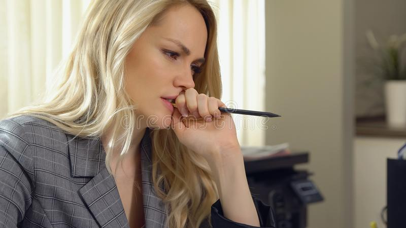 Piękna biznesowa kobieta gryźć jej ołówek w biurze obrazy stock