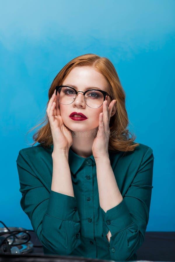 Piękna biznesowa kobieta jest ubranym szkła przy stołem patrzeje kamerę na błękitnym tle, obrazy royalty free