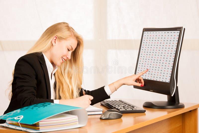 Piękna biznesowa kobieta pracuje w jej biurowych spojrzeniach w monitro obrazy royalty free