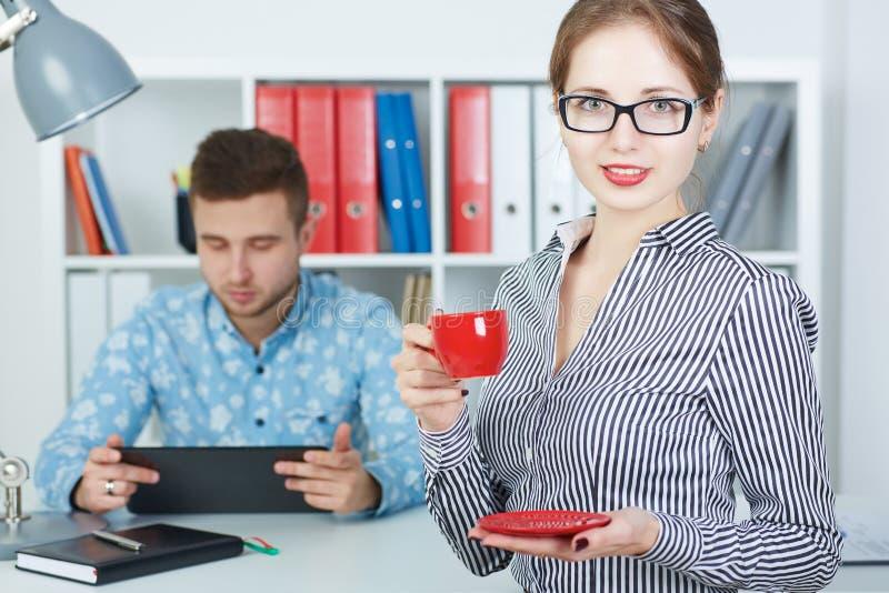 Piękna biznesowa kobieta trzyma filiżankę kawy Młodzi partnery biznesowi dyskutuje pomysły dla rozpoczęcia przy spotkaniem zdjęcia royalty free