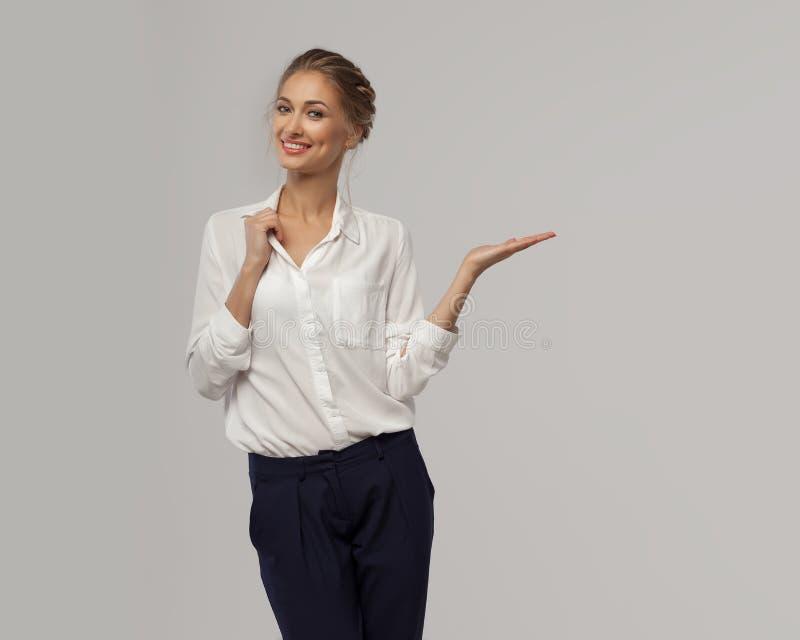 Piękna biznesowa kobieta w białej klasycznej biurowej koszula demonstruje coś na jej ręce z otwartą palmą i ono uśmiecha się obrazy royalty free