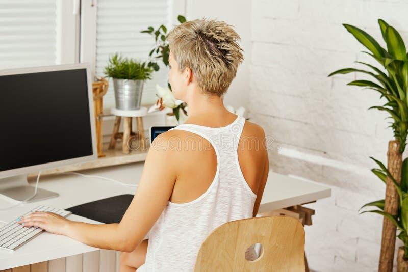 Piękna biznesowa kobieta w białym koszulowym obsiadaniu przy biurkiem i działanie na komputerze obrazy stock