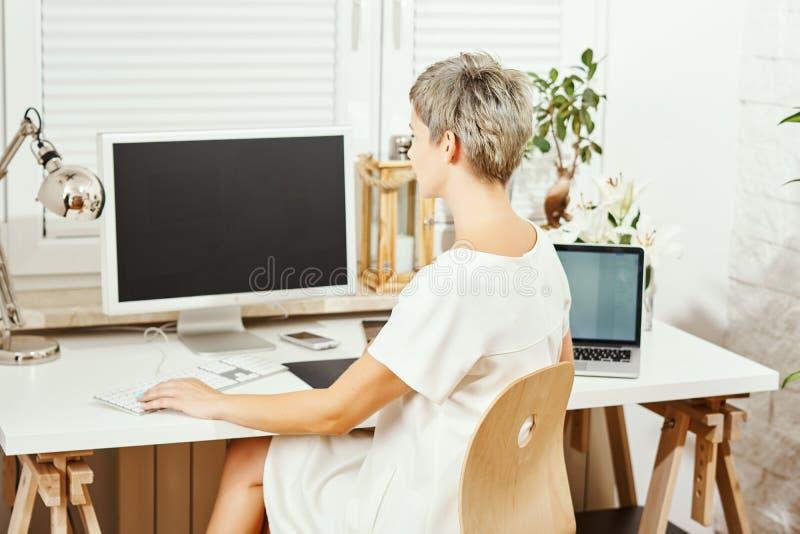 Piękna biznesowa kobieta w biel sukni obsiadaniu przy biurkiem i działanie na komputerze zdjęcie stock