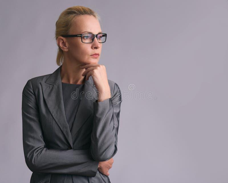 Piękna biznesowa kobieta w szkieł myśleć obraz stock