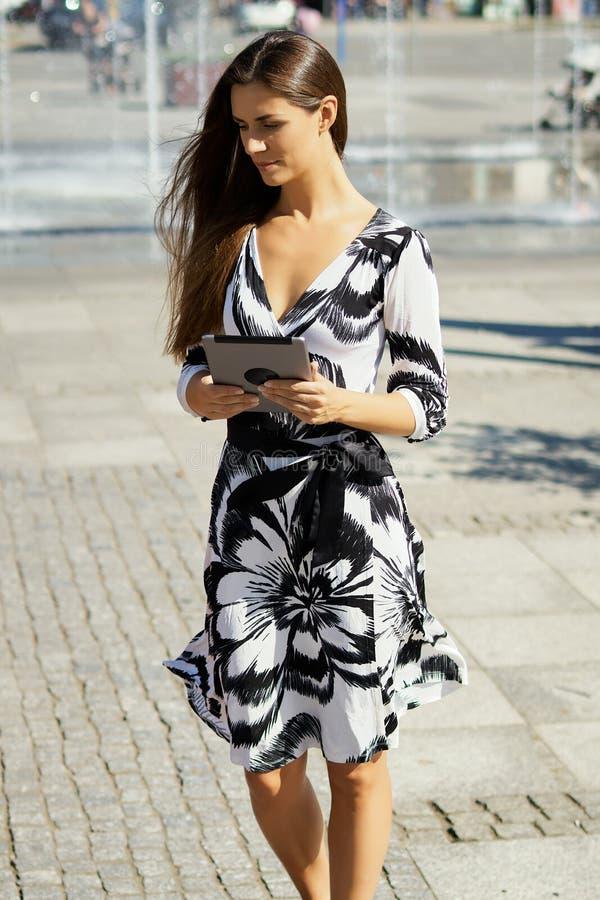 Piękna biznesowa kobieta z pastylką w ręka stojakach w pozach i parku obrazy royalty free